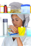 Woman Looking in Medicine Cabinet. Young woman looking at prescription bottle in front of a bathroom Medicine Cabinet. Vertical format isolated on white stock photography