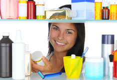 Woman Looking in Medicine Cabinet. Young woman Looking in Medicine Cabinet. Horizontal fromat isolated on white stock photos