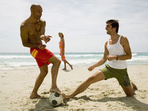 Woman looking at men playing football on the beach. Royalty Free Stock Images