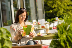 Woman looking at menu cafe bar terrace Stock Image