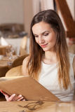 Woman looking at the menu card Stock Photography