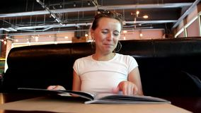 Woman is looking at menu in restaurant, turning pages stock video footage
