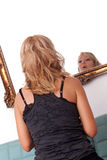 Woman looking in mirror. Pretty blonde woman seen from behind is looking at herself in mirror Stock Image