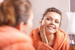 Woman looking in the mirror. Beautiful woman in bath in the morning looking at the mirror Royalty Free Stock Image
