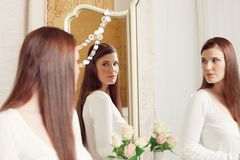 Woman looking into mirror Stock Images