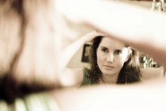 Woman looking in mirror. A woman looking in a mirror, fixing her hair Royalty Free Stock Photography