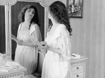 Woman looking in mirror Stock Images