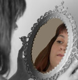 Woman looking at the mirror. Girl looking at her face in the mirror royalty free stock photography