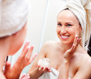 Woman looking in mirror and applying cream Royalty Free Stock Images