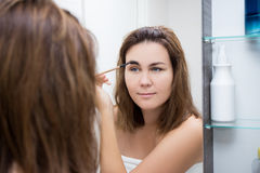 Woman looking at mirror and applying eye makeup in bathroom Royalty Free Stock Photo