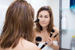 Woman looking at mirror and applying makeup in bathroom Royalty Free Stock Photo