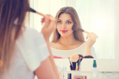 Woman looking in the mirror and applying makeup Stock Image