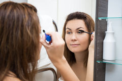 Woman looking at mirror and applying mascara in bathroom Stock Photo