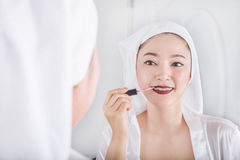 Woman looking in mirror and applying red lipstick on her lips Royalty Free Stock Images