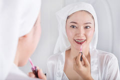 Woman looking in mirror and applying red lipstick on her lips Royalty Free Stock Photography