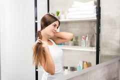 Woman doing hairstyle. Woman looking at the mirror in a bathroom and doing hairstyle stock image