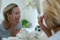 Woman looking in mirror of bathroom. At home royalty free stock photography