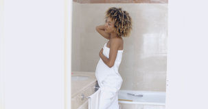 Woman Looking In The Mirror In Bathroom. Woman after shower looking mirror in the bath room royalty free stock photos