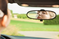 Woman looking at mirror in car Royalty Free Stock Photo