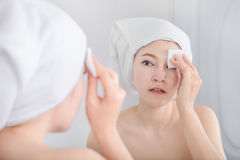 Woman looking mirror and cleaning her face with cotton stock photography