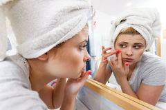 Woman looking in mirror dealing with acne Royalty Free Stock Photography