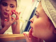 Woman looking in mirror dealing with acne Stock Photo