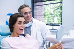Woman looking at mirror by dentist at medical clinic Stock Photos