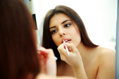 Woman looking at mirror while doing makeup Royalty Free Stock Image
