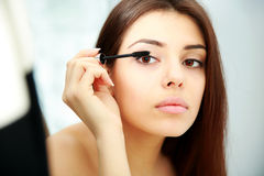 Woman looking at mirror while doing makeup Royalty Free Stock Photography