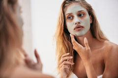 Woman looking in the mirror with face mask Royalty Free Stock Photo