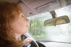 Woman looking at the mirror in her car Stock Image