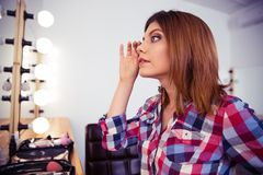 Woman looking at mirror at her makeup Stock Images