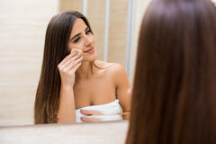 Woman looking at mirror at home and applying cream on her face. Young woman looking at mirror at home and applying cream on her face Royalty Free Stock Photo