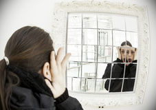 Woman looking in the mirror Stock Image