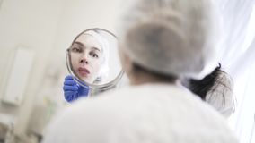Woman looking in mirror after lip injections in salon stock footage