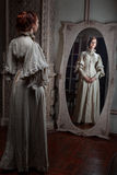 Woman looking in the mirror. Stock Image