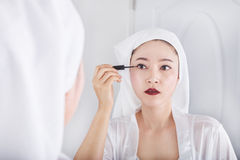 Woman looking mirror and make-up with black eyeliner Stock Image