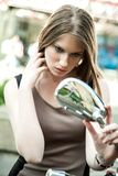 Woman looking in mirror of moped Royalty Free Stock Photography