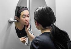 Woman looking at a mirror Stock Photos