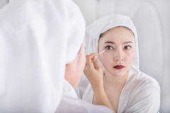 Woman looking mirror and remove makeup beside eye with a cotton. Beautiful woman looking mirror and remove makeup beside eye with a cotton swab stock photos