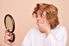 Woman looking at the mirror. Shocked and surprised middle aged woman looking at her skin and unkempt hair in the mirror Stock Image