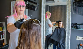 Woman looking in mirror to hairdresser combing Royalty Free Stock Photography