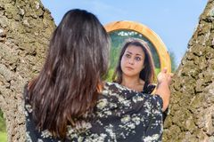 Woman looking in mirror between trees. Young woman looking in mirror between birch tree trunks Stock Photos