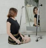 Woman looking in mirror, trying dress Royalty Free Stock Images