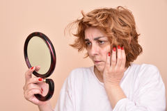 Woman looking at the mirror Stock Images