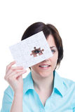 Woman looking through a missing piece of jigsaw stock photos