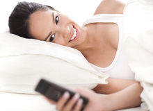Woman looking at the mobile as she woke up Royalty Free Stock Images