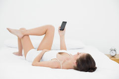 Woman looking at mobile phone in bed Royalty Free Stock Photos