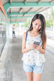 Woman looking at mobile phone and walking in light rail station. Asian young woman stock photo