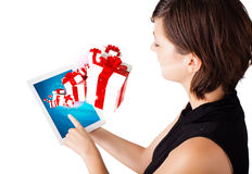 Woman looking at modern tablet with present boxes Stock Photo